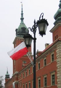 Polish Flag waving over Warsaw Royal Castle in the background