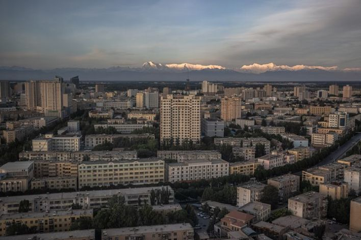 A view across a modern section of Kashgar to the snow-covered peaks of the Pamir Mountains.