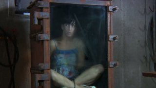 Brunette Elise Graves is locked into a small glass box Preview Image