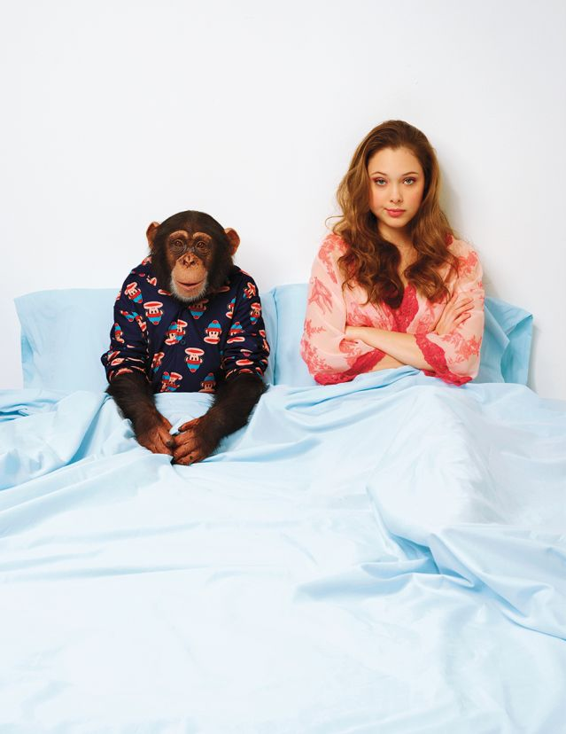 Chimp husband and human wife looking disappointed in bed