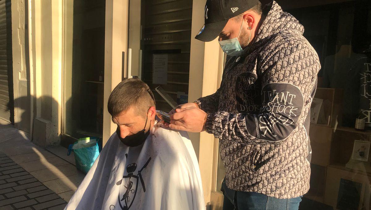 un coiffeur coupe les cheveux des sdf