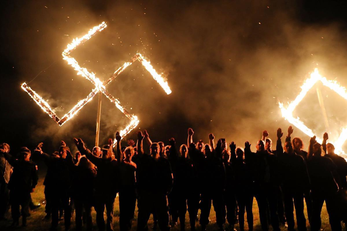 Members of the National Socialist Movement, one of the largest neo-Nazi groups in the US, hold a swastika burning after a rally on April 21, 2018 in Draketown, Georgia (Spencer Platt — Getty Images)