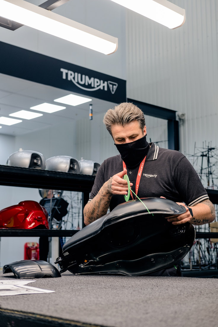 Triumph professional painter marks out the line on the Thruxton RS fuel tank