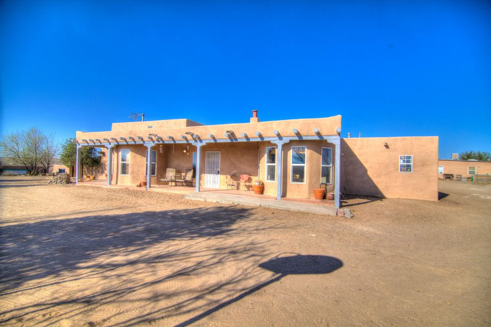 Stunning mini Ratchette in Belen NM. Enjoy stunning views and 2.36 acres. 2 car attached and tandem detached 31X34, and also a large work shop with additional storage, that could be converted into casita. Inside enjoy custom brick floors and 24'' Vigas with rough cut T&G. Amazing great room with adobe accents. Great sunroom with views and a lovely court yard with play ground. Horses and chickens are welcome.