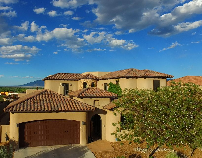 Tuscan romance abounds in the grand courtyard, complete w/ Romeo & Juliette balconies, in this Exquisite custom home in the exclusive Oxbow North gated community. This spectacular 4-5 BDR 3.5 BATH home showcases dark wood vigas compliment light walls, hard wood, large slate tile & hi-grade carpet. Gourmet Chief's Kitchen features prof-grade Wolf 6 burner stove/double oven, Subzero fridge/freezer, custom cabinetry/LG Island.  Grand Master Suites on main level offers every luxury expected! In-law suite. Office/5th BDR offers private entrance. 3 Outdoor Living Areas include outdoor kitchen & fireplace to enjoy the sweeping views of the Sandia Mtns, Rio Grande & balloons.  3 car garage offers space for all of your toys.