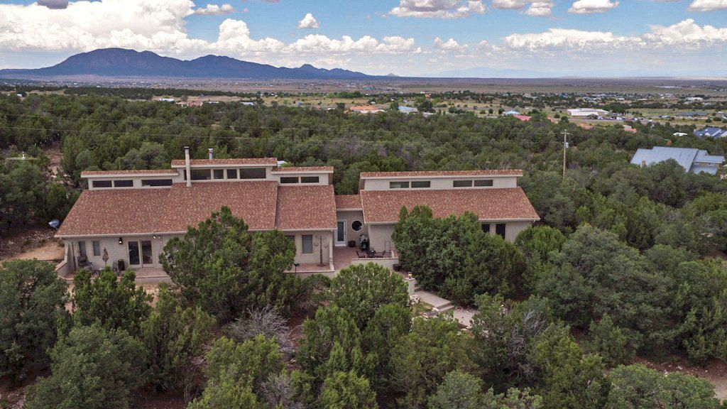 Beautiful ranch-style REMODELED custom home in the woods boasts impressive views, an open floor plan, brick outdoor living spaces, and a GUEST HOUSE all within 20 minutes of ABQ. Fully fenced 3 acres with option to purchase additional attached 3 acres, as well as a paved road leading to the property. Updates include; new stucco, updated landscaping, interior doors, granite countertops, stainless steel appliances. Four piece master bath w/his and her sinks, jacuzzi tub, and separate rainfall shower. Custom built-in office opens to loft. Pella windows and exterior doors, ceiling fans in all rooms, radiant heating, and a reverse osmosis water system.
