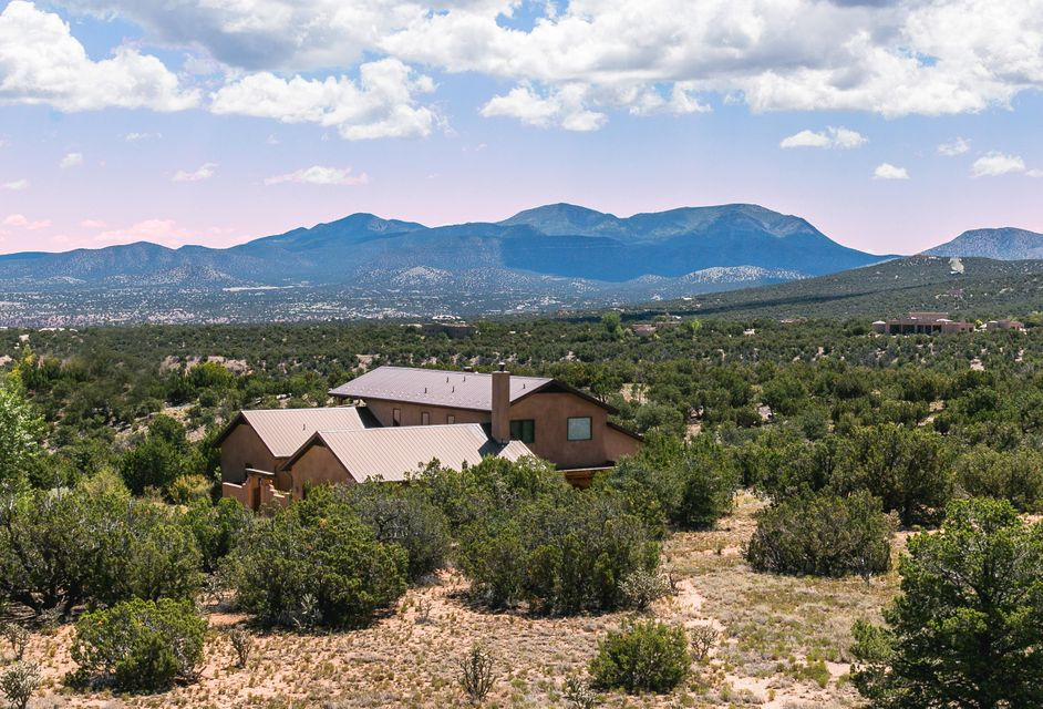 Prideful ownership is prevalent in this custom Northern NM style home. Seldom used pet free home. Enjoy 360 degree scenic views of the Ortiz , Sandia Mountains and distant city lights of Santa Fe. All living spaces and master on 1 level including a large separate den/study. The home is appointed with SW accents, tongue & groove wood ceilings, kiva fireplace, nichos, and adobe accent walls. Pella wood casement windows, large open great room dining combination. The country kitchen has maple cabinetry, corian counters, and a kitchen bar. Guest area located upstairs along with a covered deck perfect for star gazing at night. Enjoy the perks of country living with trails and open space nearby. Schedule your tour of this home today!