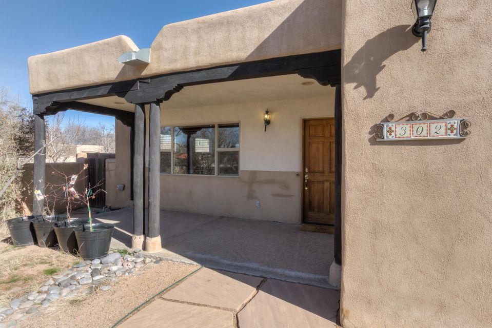 Great Location! Great Home! Gorgeous Pueblo style architecture featuring brand new York Refrigerated AC unit and brand new York Furnace! Tongue & groove ceilings, vigas, beams & corbels. Skylights throughout, wood burning Kiva fire place, Large spacious kitchen with granite tile counters, breakfast bar, Large Picture Window. New carpet in all three the bedrooms, recessed lighting, wood & tile flooring. Large Master Bedroom with private covered patio with flagstone pavers. Large laundry room, xeriscaped backyard with rear access, Oversized single car garage with work bench. Check out the link to the 3-d video of this home.