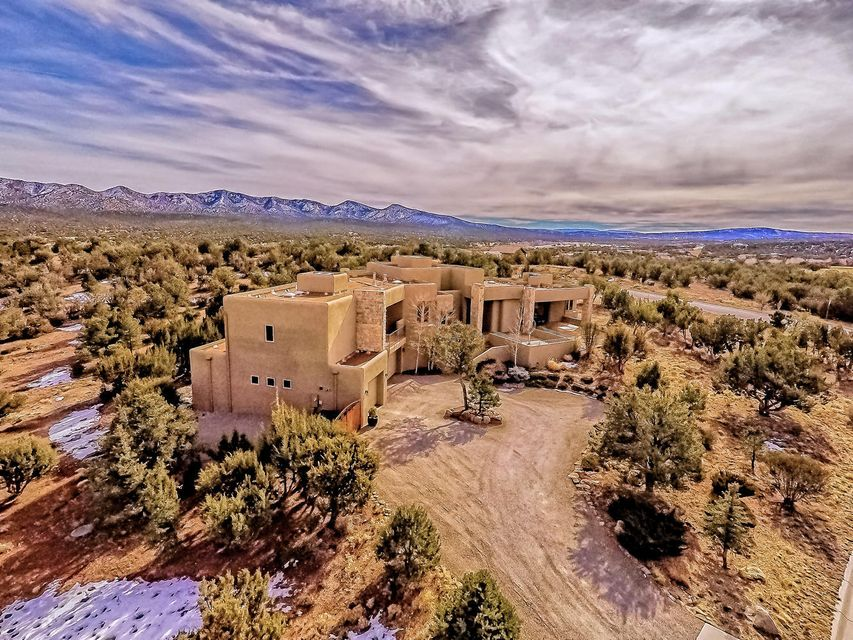 This exhilarating and exquisite home was designed to meet the needs of the sophisticated homeowner. Boldly embracing the architects vision of blending chic modern w/nature's beauty, it is a highly functional retreat in the desirable golf-course community of Paa-Ko. It offers mountain views, a quick drive to play golf or eat at The Grille & convenience to either Albuquerque or Santa Fe. This private refuge offers 3 BRs, a luxurious Master Suite w/exercise room, office and a fabulous kitchen. Ideal for entertaining inside or out. Heated and cooled 232 sf workshop, 4-car garage, tons of storage, RV parking and much more. Seller will consider TRADE OR CREATIVE FINANCING. Priced far below replacement value. This residence is paradise, utterly romantic and remarkable in numerous ways. Come see!