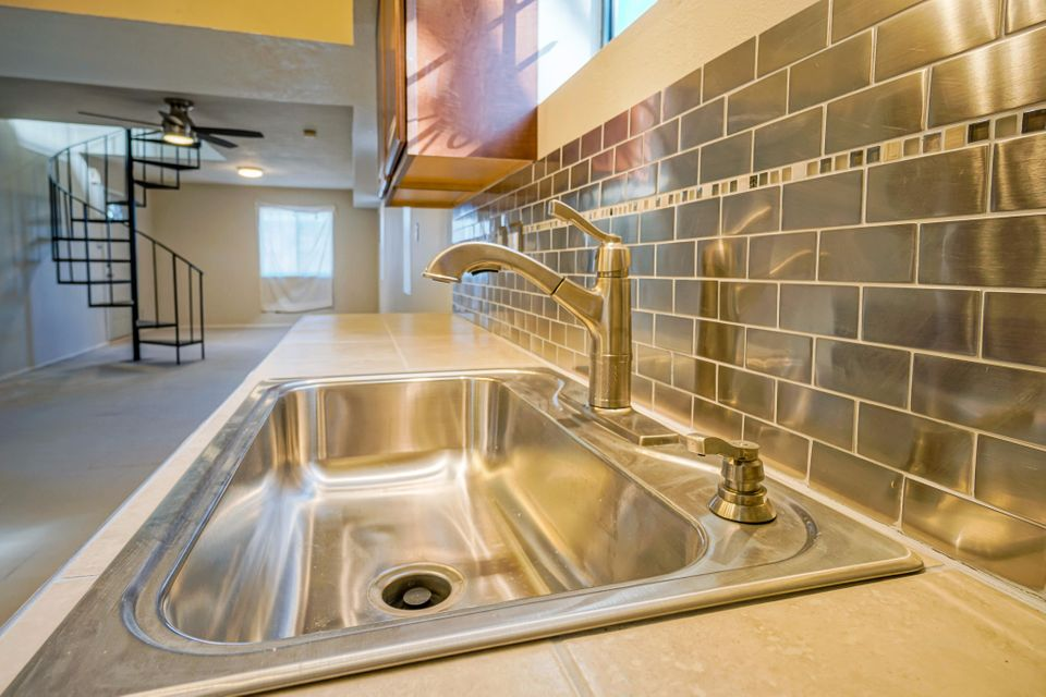 Adorable 2-story, Northern-NM-style home in heart of Old Town minutes from Plaza. Property exterior is old-world,traditional NM: interior is modern w/minimalist-metalic motif. Main level:great room w/nice country kitchen is newly updated:rich,dark wood-custom cabinetry,stainless-steel appliances,new ''green'' tankless-hot-water heater & full BA/original,stain-glassed-accent window,new slate-style 12''field tile & new stack washer/dryer combo.Spiral staircase to 2nd story: loft w/master BR, 1/2 BA,2nd BR.Staircase from the rear of the property to second story (separate entrance) w/portal/deck.Updates include new satin finish hardware & tile/carpet flooring. The property has access from both Hollywood NW & road off Central NW. Just several blocks from the acequia,Aquarium,Botanic Gardens,etc