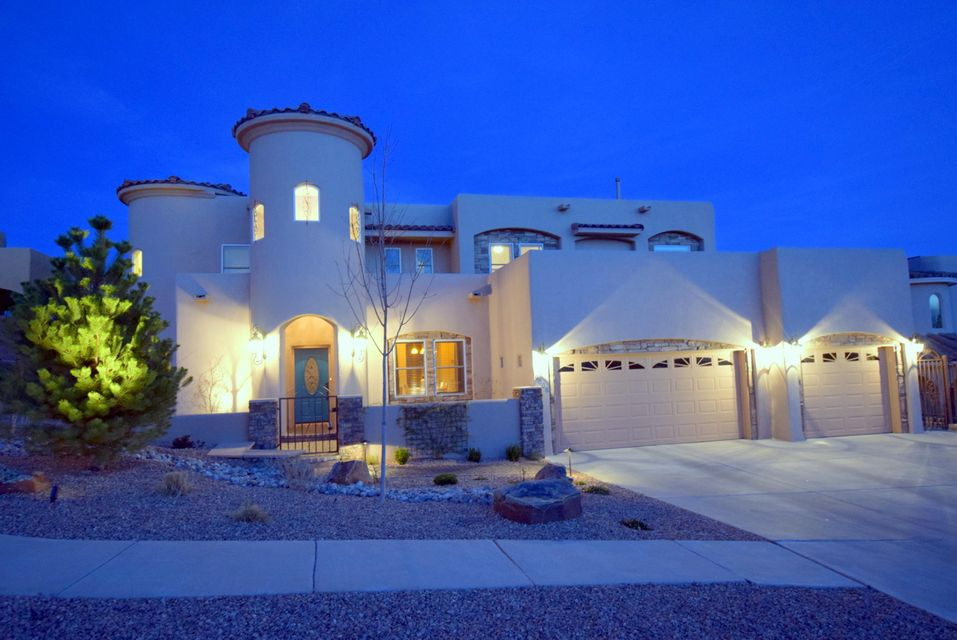 Located in The Knolls of Paradise Hills this custom home is immaculate. The unobstructed views of the Sandia Mtns and city lights can't be beat! Built with two master suites - one up and one down, large open living areas, designer kitchen with a big granite island, oversized 3 car garage, downstairs office area and a 2nd upstairs living area complete with a kiva fireplace and access to the impressive covered deck.  The owners have recently had all of the landscaping professionally installed  with brick walkways, stone work and a beautiful courtyard wall in the front.  The backyard has beautiful plants and trees and just enough grass. Some of the other recent improvements include a water softener, remodeled laundry room, new doors, low E window tinting, new lights and fans. Exceptional!