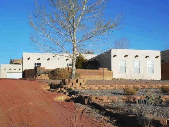 Custom adobe style home on a half acre+/- home site in the Rio Rancho Estates community north of Albuquerque. Many upgrades including hardwood and tile floors, French doors to large courtyard, granite counters and detached 2 car garage. Beautiful long range views.