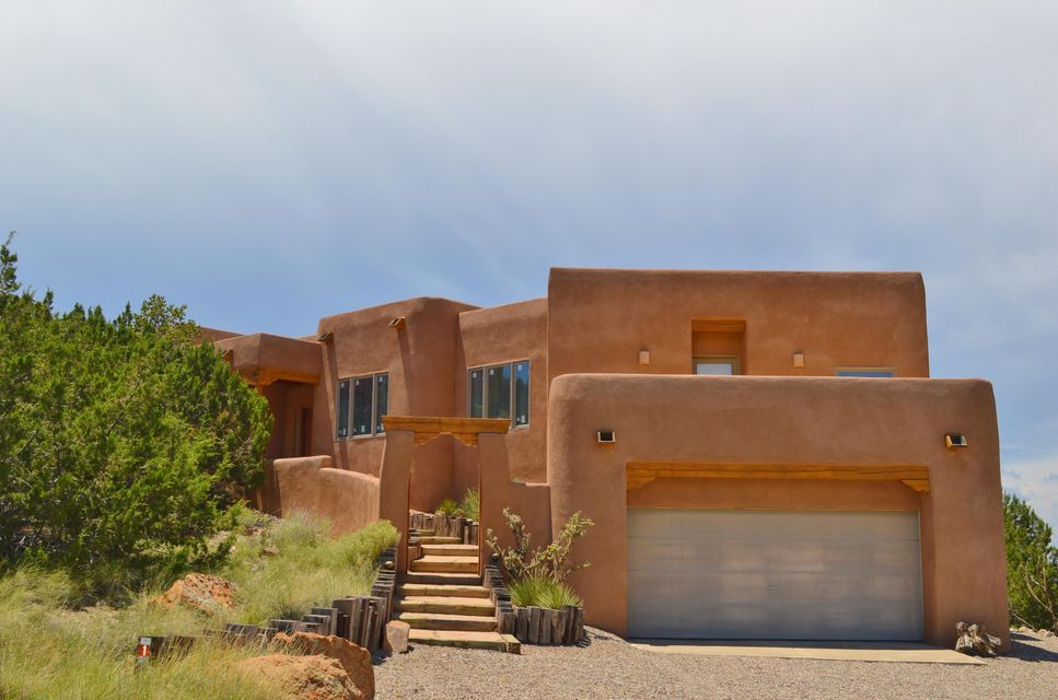 Custom pueblo home has spectacular all around views. Lovely floor plan w/ great room concept wonderful for entertaining inside & out. Gorgeous wood ceilings in Living Room, Dining Room, Kitchen & front and back covered patios. Seller has upgraded home w/ the following: many newer windows, new microwave, new oven & newer deck material off master bedroom. There are two custom kiva fireplaces. The very large Master Suite is separated from other bedrooms & has a private deck w/ spectacular mountain views. Master Bath has a jetted tub w/ terrific views & a two-person shower. The finished garage is very large & has lots of storage space plus an enclosed storage room. This extremely well priced home is located in beautiful Vista de Oro Subdivision w/ very quick access to the National Forest.