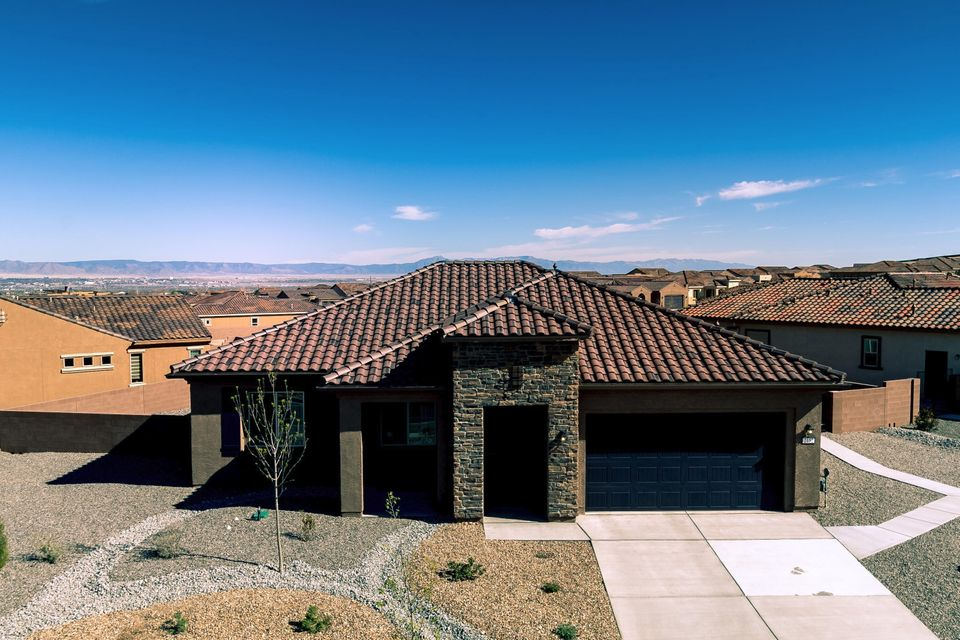Seller transferred and their loss is your gain. With over $15,000 in landscaping by Hilltop, $68,000 in options & a $23,000 premium view lot, you couldn't build this home for the price of this one-year young one. Stunning views of the Sandia mtns & city lights make every morning & evening extra special. Spacious kitchen includes a huge island, SS appliances, pantry & extensive counter area work space with granite tops. Mstr suite features double sinks, W-I closet, & an over-sized shower with seating. Laundry rm offers cabinets w/ granite countertops for extra storage. The gated, active adult (55+) community includes a fitness center, pool & spa, sports courts & over 6 miles of walking/biking trails. VA loan is assumable at 3.5%. This is a terrific home in a lovely neighborhood!