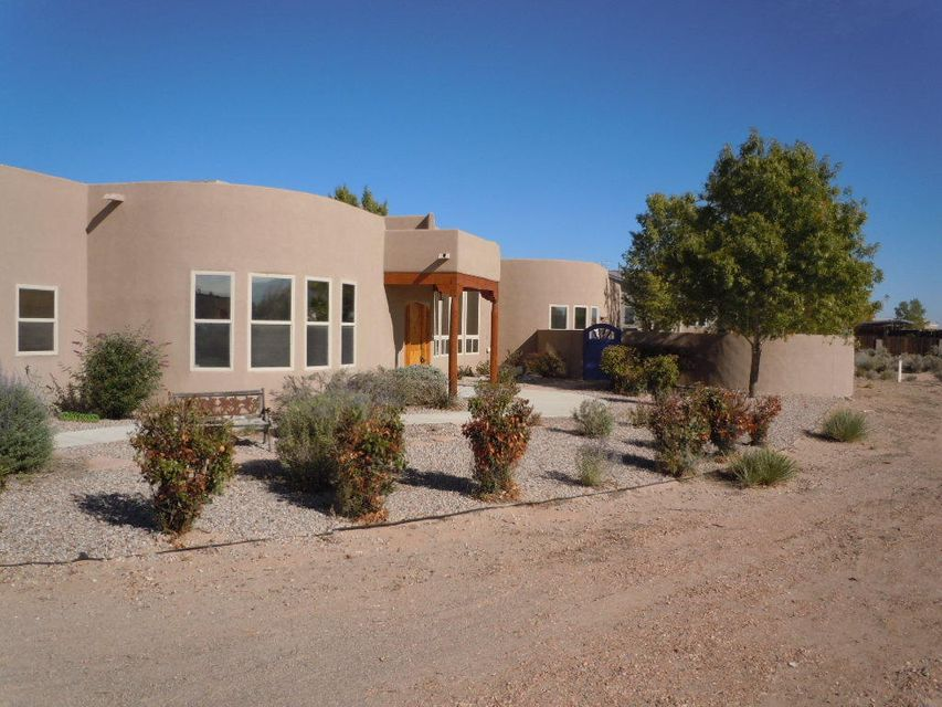 Come home to this fabulous custom pueblo style home on a peaceful cul de sac. Enjoy the forever views from your patio & on those chilly nights, cozy up to the outdoor kiva fireplace. A flowing floor plan includes a  gourmet kitchen, formal & casual  dining areas, 4 bedrooms + office with a wet bar & a living room with a gas log fireplace. Special features include stained concrete floors, vigas, beams & nichos, inside & out, curved walls & lots of windows for natural light, custom wood doors & decorator paint throughout. Master suite opens out onto it's own private courtyard with mountain views. An oversize 3 car garage has room for cars + work benches.