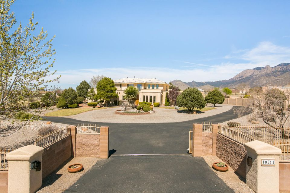 Elegant Mediterranean Style Estate beautifully situated at the base of the Sandia Mountains in highly sought-after North Albuquerque Acres. This 4,195 sq. ft. home is perfectly positioned on the .89 acre lot to take advantage of the city views as well as the mountain views (600 sf of balconies) and is gated as well as completely walled/fenced. The floor plan is so engaging and convenient, with two luxury owners retreats (one on the main level and one up-stairs), two additional bedrooms PLUS a study AND a separate office with private entrance and separate Mitsubishi cooling unit.  If you entertain, you'll love the flow of the 2 living areas, (one with a wet bar and fireplace) the dining area and breakfast nook along with the covered patio for outdoor entertaining.