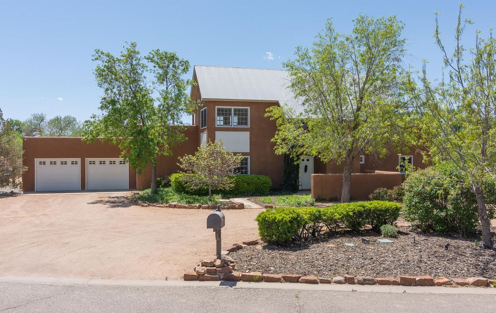 You will fall in love w/ this beautiful, spacious home in the North Valley. Enjoy a lush, beautifully manicured yard, private basketball court, lg covered patio & winding path. A feeling of privacy yet in a neighborhood. Close to walking/bike paths. Part of 1 acre lot is very open & can be used in a variety of ways. Even room for a horse! The gorgeous kitchen w/ granite, stainless appliances & brick floors is open to great rm w/ Kiva fireplace & dining rm. Light & bright throughout. Newly renovated bathrm in  private, upper mstr suite. Beautiful custom cabinetry w/ plenty of storage added in upstairs loft. Spacious mstr bdrm offers great view windows. 4 bdrms downstairs w/ 2 full bathrms. 2 of the bdrms & 1 bath are in a separate wing. Den w/ custom cabinetry opens to patio.