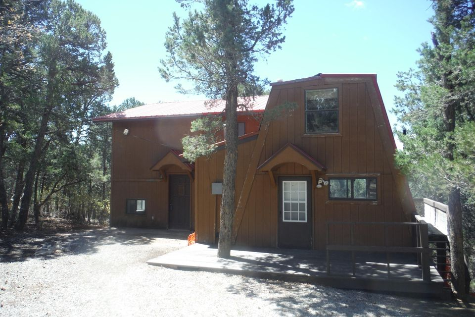 Great opportunity in the wooded parts of Tijeras. Three bedroom two bath cabin with brand new septic tank, hauled water unit, furnace, new carpet, and fresh paint. The house offers a loft as well as a kitchen with an island, and plenty of natural light!