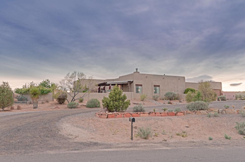 This magnificent 1.6 acre property is the epitome of privacy & serenity. Enjoy the Sandia Mountains by day, city lights by night. Southwest Pueblo style includes high ceilings beautiful arches & stunning tile. The wood burning kiva fireplace looks like a Georgia O'Keefe masterpiece. Grand room with plenty of room for furniture & entertaining.  Grand Room & family room are open to kitchen. Gourmet kitchen features beautiful cabinetry, hard surface counter tops, plenty of work space. The master suite is a private oasis to relax & renew. Enjoy your favorite beverage on the Southwest style patio. There is a small vineyard & fruit trees on the property. Bring your horses & other pets. Minutes from shopping, dining, movie theater & easy commute to Albuquerque.