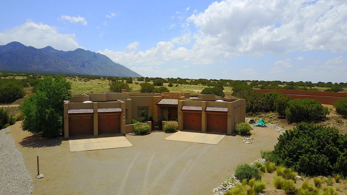 New Price! Unique, one of a kind views. Beautiful Southwest style, custom built, green home in Placitas with clear views of the Sandia Mountains on 1 acre of land.  Less than 10 years old and very well maintained. It is next to a National Forest and mins from I-25.  4 bedrooms, 4 baths with a 4 car garage!!  Perfect for a car enthusiast or extra gear. Possible 5th bedroom with sink and small refrigerator.  Beautiful stone work throughout. An open floor plan for entertaining.  Large kitchen with commercial grade appliances, bar and breakfast area along with a large formal dining room 30 X 13.  The master bedroom has a large on-suite bath with sitting room/study, gas fireplace and his/her closets.  Sit in your jetted tub enjoying the views or enjoy time in an extra-