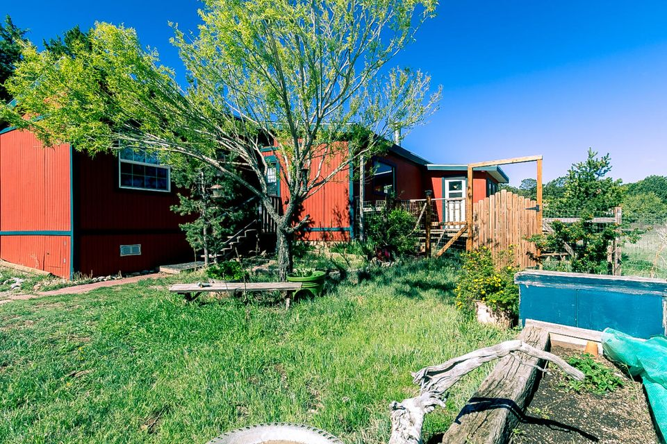 Energy efficient, low maintenance home on just under 3/4 acres in the East Mountains. Beautiful lot offers wooded, landscaped and meadow areas along with picturesque views. Napolean wood stove with energy-efficient propane heater, on-demand tankless hot water heater, evaporative cooling. Two bedrooms, 3/4 bath, living room, and sunroom. 11'x9' laundry room could be used as office. Eat-in kitchen has gas stove/oven, refrigerator and dishwasher. Fully fenced, large deck, raised garden beds, trees, storage shed. Community water with an RO system. This is a short sale. Property sold ''as-is''.
