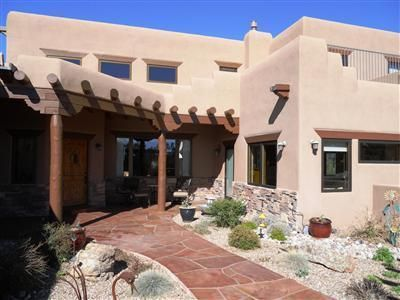 Exceptional Value here! A stunning celebration of Contemporary Southwestern Charm! Green built with solar! Sweeping Sandia Mountain Views!Soaring ceilings in Greatroom with custom fireplace!A real Chef's Kitchen with Knotty Alder cabinetry, loads of granite slab counter space and Stainless steel appliances. Generous informal dining space. Good sized bedrooms with walk-in closet spaces.  Private Master suite on the main level with lavish master bath featuring dual vanities, jetted tub and separate steam shower.Hot water and electric solar panels! Great outdoor living spaces, perfect for entertaining! Large view deck! 3 car Oversized garage! Top of world feeling at this home! A must see and an amazing value. Quality abounds!