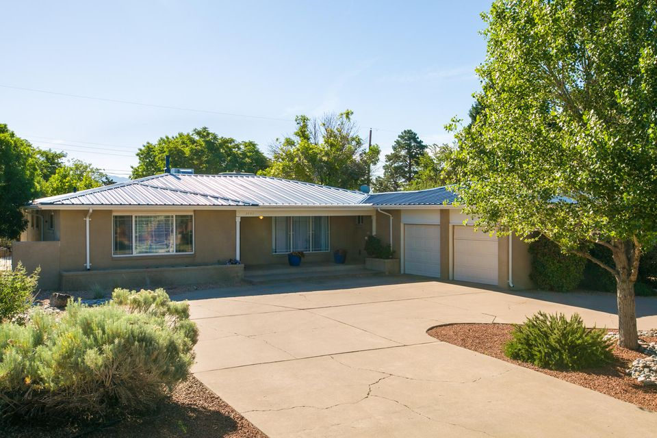 Modernized and desirable Altura/UNM area home on peaceful corner lot. Updated kitchen includes stainless appliances, island, glass-front cabinets, granite, and new fixtures. New paint, new carpet, gleaming wood floors, newer windows, and more. All bedrooms have a bathroom and lots of closet space. 4th room with 1/2 bath could be a great study/craft area. Covered back patio opens to a serene yard with an outdoor fireplace. Oversized garage has storage and shop space. Sparkling clean... inspections complete!