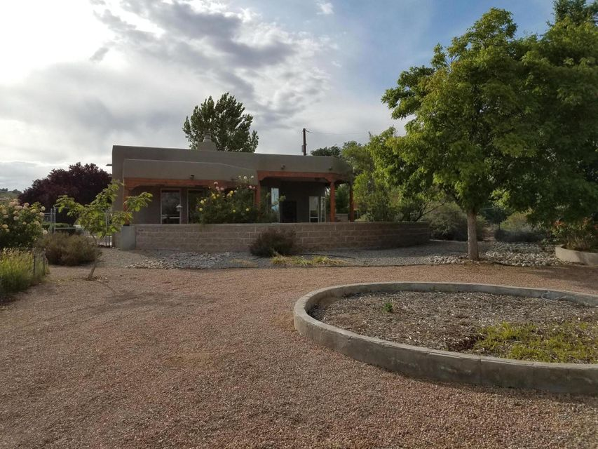 This lovely Rachel Matthews custom home is on a private paved road and features mountain views, wood beam and plank ceilings in the great room, kiva fireplace, 18x18 natural stone tile, custom cabinets and granite counters in the kitchen, wood plank floor in master. 3rd bedroom is perfect for an artist studio with an adjoining 20x20 office/gallery and it's own entrance from the courtyard. Perfectly landscaped and fenced with room for RV, horses, etc.
