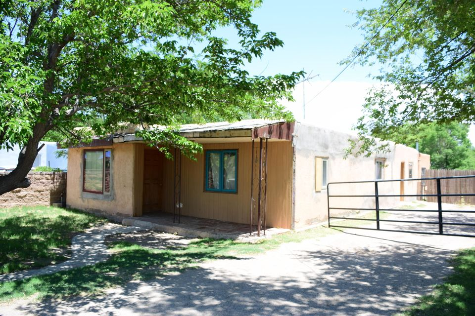 There is an existing adobe home on the property with an added area that includes a kitchenette. There is also a storage container in the back yard. This property is zoned commercial.