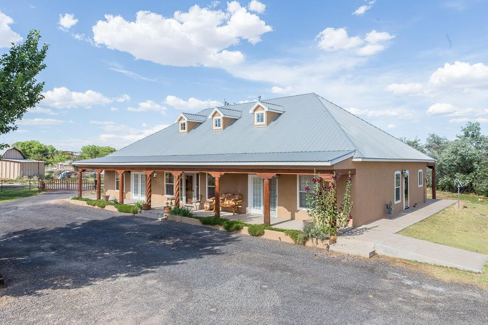 Beautifully upgraded Northern NM style custom home set on 1.18 gated acres in the greenbelt.Detached 2 car finished garage with huge open space, and 851sqft,inlaw suite, not counted in total Sqft. Property features 4BR 4BA plus an office w/private entrance. 2-way gas log kiva fireplace, custom wood doors w/copper inlaid interior doors and matching cabinets.Vega and wood cathedral ceiling in LR.Glass tile backsplashes, custom granite island/counters/sills and new wall oven in kitchen, fridge stays.Granite in newly remodeled baths.Custom wall finishes.Full front portal and 10x70 back portal/porch. New carpet in MBR,ceramic tile,quality wood flooring,and many more custom touches.Newer A\C-heating combo unit. 30x75 barn with a ''Cantina'' style mancave, 2-15x15' stalls, hay storage and parking