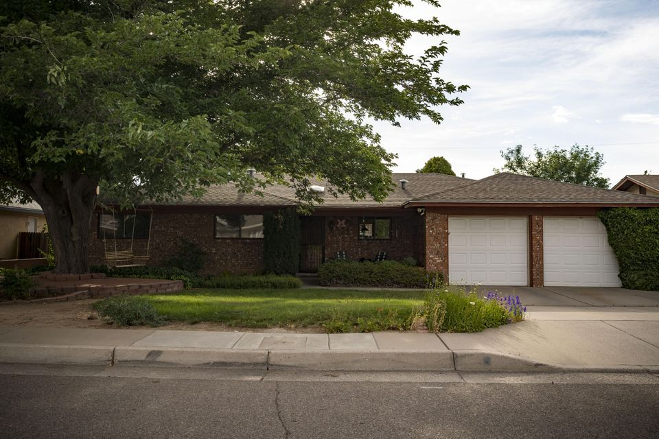 Welcome Home! Amazing find in the Albuquerque Uptown Area! Very spacious with a flowing floor plan.  Clerestory windows & skylights invite the natural lighting throughout.  Beautiful kitchen with eat-in breakfast nook.  Solid oak cabinetry with pull out shelves with sile stone countertops.  The kitchen backsplash features Santa Fe artist Davila Brodsky tiles. On those cold winter nights, snuggle up next to the wood burning fireplace.  Enjoy your very own sanctuary of lush vegetation as the backyard allows for pure tranquility.  It also offers a built-in BBQ grill and a lovely pond with goldfish.  Original owners have definitely shown pride of ownership.