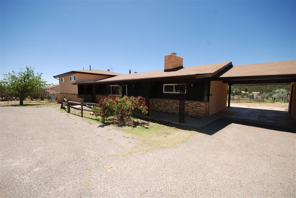 Great family style home in desirable Sandia Park. Almost 2 useable fenced and cross fenced acres for all your animals. Even a barn at the back.  New stucco and exterior paint and new windows for a maintenance free exterior. Large lving room, plus a family room with fireplace.  Country kitchen is sunny with lots of cabinets and countertops.  Split level plan has spacious master bedroom and 2 other bedroom upstairs.  Lower level with another fireplace makes a great kid's play room or entertainment room.  Extra  storage and laundry room.  Cement patio out back.  Detached one car garage is more of a work shop.  Extra concrete slab to west of workshop for RV parking or another garage.