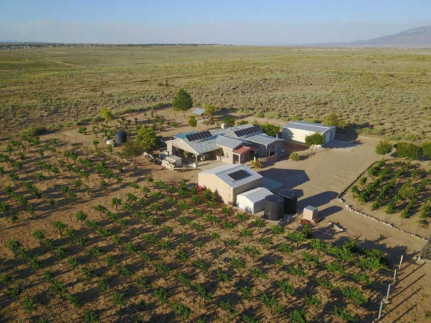 This solar powered home is set upon 2 quiet acres, totally enclosed w sprawling vineyards & amazing forever views in all directions. The property has 2 car detached garage, 1 car outbuilding/warehouse AND 2 car carport for all your storage/winery & workshop needs. The 1449 sq foot home is charming inside w warm paint colors & huge country kitchen, 3 possible bedrooms, a 187 sq ft tasting room in the entry (not included in the total) could be a 2nd living space/office. If that isn't enough, there's an 700 sq ft basement that stays a constant temp all year round. The possibilities are endless on this sprawling ranch. This quiet oasis is still only min. from town making it conveniently located close to local restaurants,shops, movie theaters. New solar well pump just added. Come see it today!