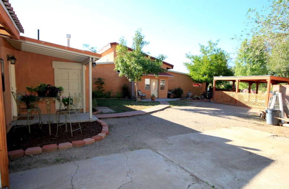 GREAT INVESTMENT! Live in one home;rent the other! Two homes perfect for multigenerational family,communal living, VRBO, B&B, or assisted living with proper permits. Lot is over 1/2 acre of irrigated land in a quiet North Valley location. The front home,built in 2011, has a fabulous Master Suite with private patio, in-floor hot water radiant heat, clerestory windows in the loft with awesome sky views and lots of natural light, concrete floors and countertops, custom cabinets, loft/office, 3-car garage. Original home has 3-4 bedrooms, office, updated kitchen, sunroom and large living/dining room, two updated bathrooms. 4th bedroom has kiva fireplace and would also make another great living area, office/study, hobby room. Property will soon back to Los Ranchos green Open Space! Great BUY!
