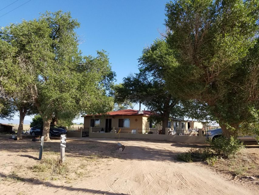 Get out and see this oasis on the prairie for sale in central New Mexico! Very specious and updated home with open floor plan is clean and move in ready. Updates to include newer windows, updated bathrooms and country kitchen, ceramic tile and laminate wood floors, french doors, jet tub, wood and gas stoves, and much more. Bring the animals as the 9.6 acre lot is partially fenced with plenty of room in the metal building for tack and tools. No high propane payments as this property is set up on natural gas. Enjoy your morning coffee on the covered patio watching the colorful sunrise and you may just witness a cattle drive! Get out and see this one before it is gone! Seller is offering to pay for a 1 year home warranty for the buyer!