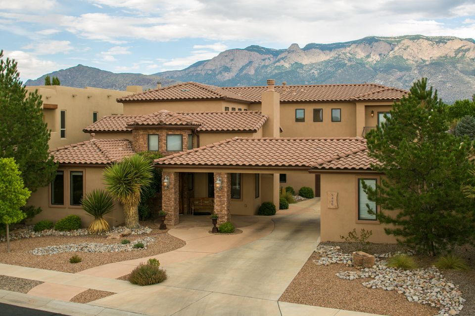 Custom elegance abounds in this beautiful Tuscan style home w/views of the Sandia Mountains!   Oversized lot, gated community, 4BDR/3 FULL Bath, 3CG plus carport with approx 3451 of living space.  Guest suite/office w/full bath on the main level.  Two living areas plus loft.  Custom finishes & fixtures throughout, new tile flooring, beam ceiling, REFRIG AIR.  Gourmet kitchen featuring Subzero fridge, two ovens, gas cooktop, granite countertops, large island & bkfst nook and walk-in pantry.  Private master suite features a double headed shower, jetted tub, gas fireplace, views, his & her vanities.  Secondary bdrs have Jack-N-Jill bath & balcony!   Private backyard has a covered patio, lush grass, waterfall, trees, shrubs and VIEWS!  Desirable neighborhood of Estates at Desert Ridge Trails.