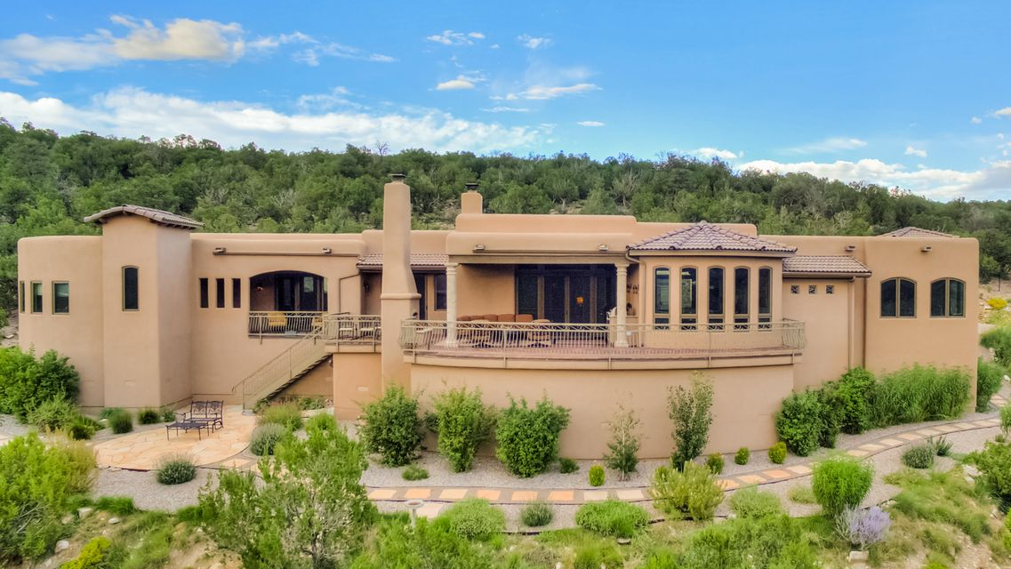 Like having your own personal resort! Like sunshine and snow? You'll have the best of both worlds here.  Skiing, golfing, hiking, biking & Santa Fe only minutes away.  Stunning custom 1-story home with breathtaking views features a sauna and steam shower.  Refrigerated air; fireplace; solid plank hickory flooring; custom-made Alaskan alder wood cabinets, bookshelves, & closets; gourmet kitchen w/Thermador appliances & granite counters. Master suite features jetted tub, separate over-sized shower, his/her toilets & sinks, spacious walk-in closet, motorized window shades, covered deck & private courtyard. Ensuite bath in 3rd bedroom.   Deck w/fireplace & built-in grill. ADA accessible no-step entries & wide doors. Oversized 1361 sq ft 3-car garage w/durable epoxy flooring.