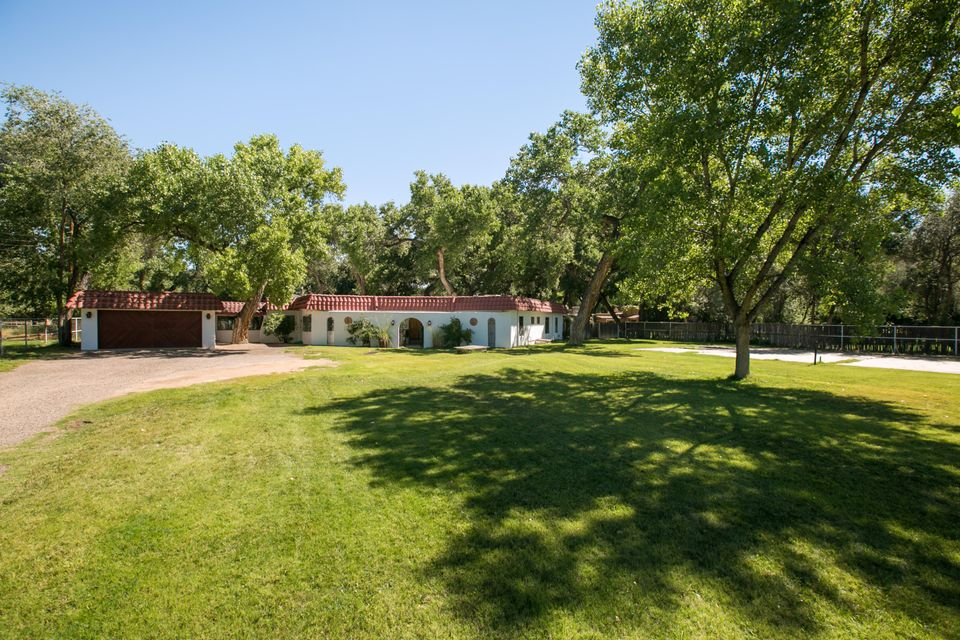 Fabulous Corrales hacienda in a desirable eastside location! Nestled under mature cottonwoods, this well maintained home offers a flexible floorplan. A separate mother in law quarters, or at one time wasused by a baker to cater. Large gracious and spacious living areas. Living room features a step down,  brick floors, kiva fireplace, vigas, & a gorgeous view of the lush yard. An elegant formal dining room, a kitchen that is awaiting for you to turn into your dream kitchen, large family room that boasts the outside lush grounds, a huge recreational room w/hot tub & room for a pool table! A separate gardening shed. 2 car garage.  New roof w/warranty. A truly beautiful property.  Access to the bosque & trail system. South end location for the great escape to city conveniences.