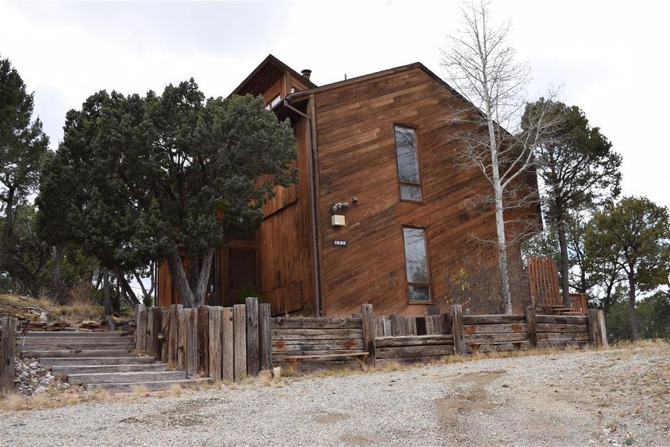 Secluded, woodsy mountain home on 2 lots in Sandia Knolls Sub'd. Water sytem, oversized detached garage/ workshop. Must see!