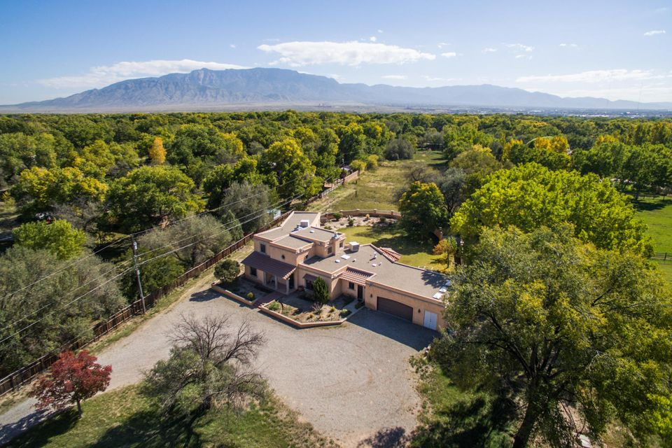 Stunning custom home located at the end of cul-de-sac on the east side of Corrales Rd.   Features include: striking foyer, formal dining, spacious kitchen w/island and large breakfast nook, office/den, mstr bath w/jetted tub and separate shower.  Raised ceilings in living room with picture windows.   3 car garage w/two bays for vehicles and 3rd bay for storage.  Backyard w/large open patio.  Tranquil approx. 2.87 acre lot hosting views of the Sandia Mountains and two stall horse barn.