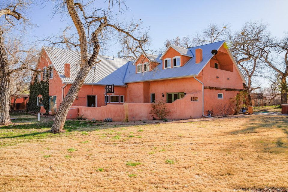 Serene, Pastoral Setting for This Northern New Mexico Style Home on 1 Acre on the East Side of Corrales Road ** Towering Cottonwoods, Expansive Grassy Yard and Space for Horses ** Flexible Floor Plan with a Second Floor that Could Be Configured in So Many Ways ** Great Kids Area with Bedrooms, Baths and Play Areas or Extended Family Quarters ** The Downstairs Area Has All the Authentic Touches with Brick Floors, Wood Beamed and Decked Ceilings, Tile, Hardwood Floors, Kivas ** Fabulous Open Kitchen with Gas Stove, Tile Accents** 3 Fire Places ** Sunroom ** Lovely Pond Area ** Gated Entry  **Refrigerated Air ** Sellers Are Obtaining Bids on Stucco ** Make This Your New Home..