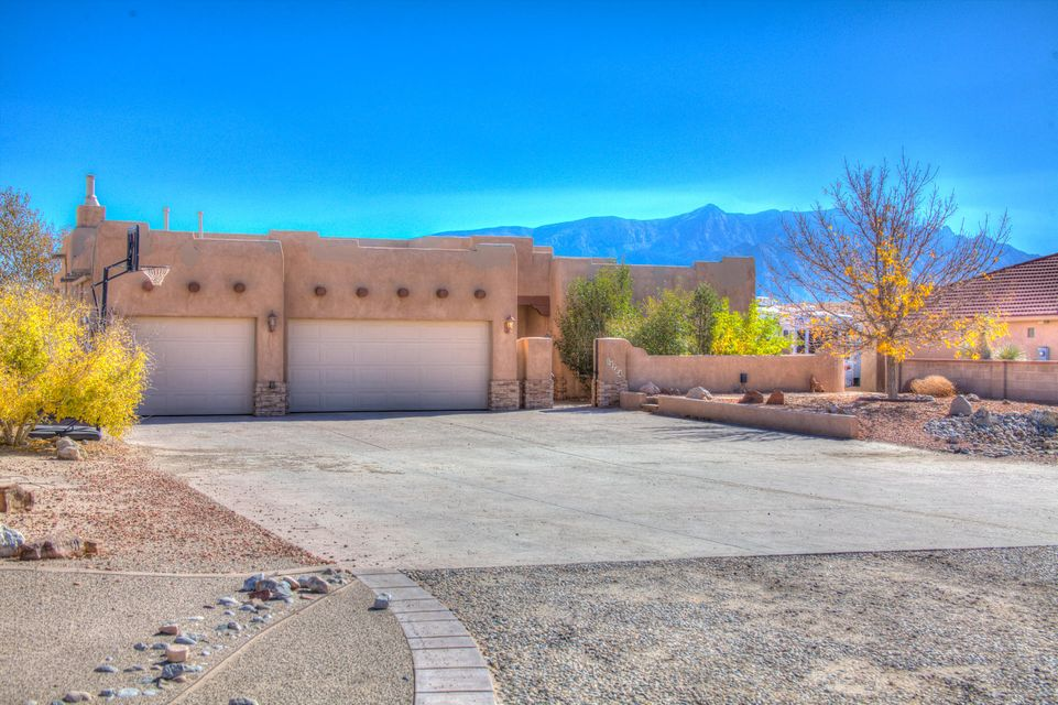Views, Views, Views! From this custom built 4BR Pueblo Style home, with 3 car garage, on 1/2 acre. You will enjoy the low maintenance open floor plan with 2 living areas, split bedroom floor plan and beams. The floors and counter tops are colored concrete for strength and endurance. The radiant heat will keep you warm in the winter and the high insulated concrete walls will help keep cool in the summer. The back covered patio opens to a huge backyard with great views of the Sandia Mountains, landscaped grass area and water fall fountain. This home can not be replaced for the price! Call to schedule your private showing today!