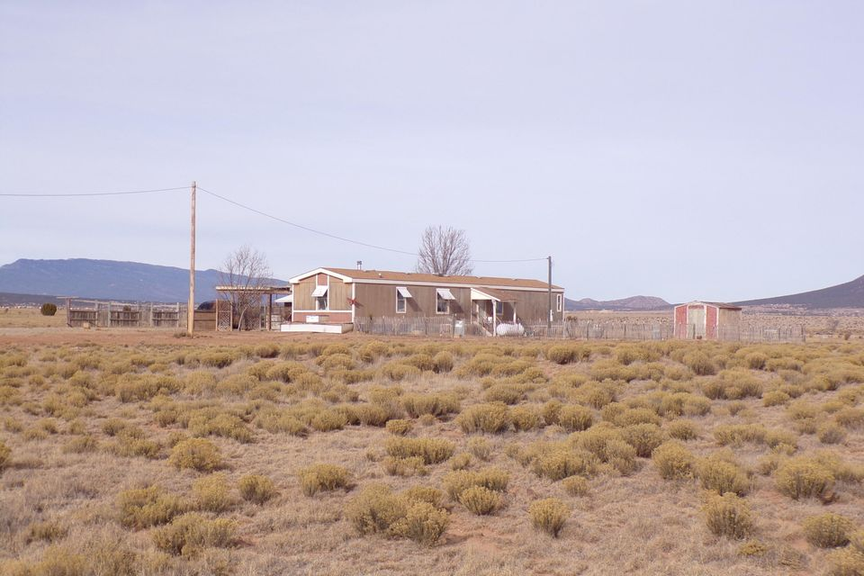 This New Mexico country home is an equine property with a 3-bedroom manufactured country home in Edgewood, NM. The home sits on 15 acres of grassland for your horses. Albuquerque and Santa Fe are less than an hour away. The property is partially fenced with a fully fenced dog area. There is new carpet and paint throughout and the owner is working on new stucco and outdoor paint.  This is the country lifestyle at its best with major shopping facilities just minutes away.  Don't miss the expansive views of the Sandia Mountains. Great place to raise a family in this small town America community.