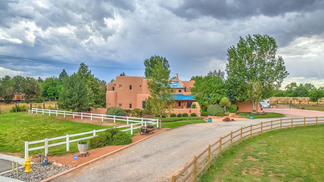 Exceptional equestrian property on a private cul de sac w/ access to the Paseo del Bosque trail. Ride your horses out the gate. This exquisite custom home is filled w/ beautifully crafted finishes rarely found in a newer home.Custom ceilings w/ vigas, latillas and a barrel vault. There are two incredible master suites, one on the main level and another upstairs with a private deck with stunning views of the Sandias.  The lower level also features an office or bedroom adjacent to a 3/4 bath. There is an attached guest suite w/ a private entrance, deck & kitchenette. Five fireplaces, a chef's dream kitchen, a grand entry & great room, a tranquil family room, library/music room, sunroom, casual & formal dining.The exterior features courtyards, covered portals & all weather gazebo & hot tu