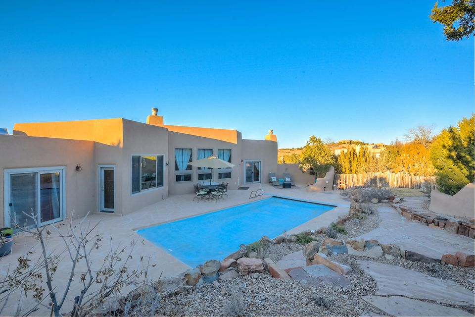 POOL SEASON IS HERE!! INCREDIBLE IN-GROUND GUNITE HEATED SALT WATER POOL W/ AUTOMATIC SAFETY COVER accents the backyard of this Custom SW Home w/ Detail and Design at its Best! The Interior exudes Santa Fe Ambience with the High Beamed Tongue and Groove Ceilings, Vigas, Corbels, Exposed Adobe Accents, Saltillo Tile Flooring, and Gourmet Kitchen w/ Chef's Downdraft Gas Stove, Breakfast Bar, Cozy Breakfast Nook. Radiant Floor Heat, Large Master Suite with Separate Shower/Jetted Tub add to the luxurious use of this versatile floorplan. Backyard is professionally landscaped  for entertaining! Mountain Views!Courtyard Entry Accented w/ Natural Rock,Custom Koi Pond, Native Plants greet you as you enter this Placitas Hacienda. An oversized 3 Car Garage has added work space is perfect for storage