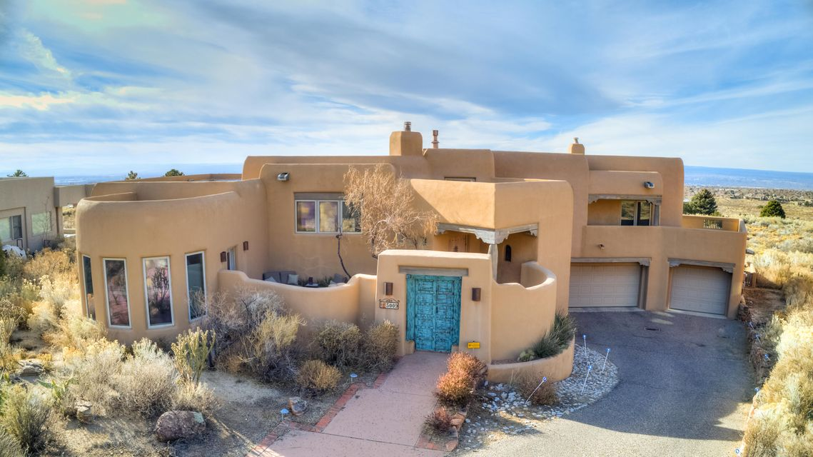 This luxurious High Desert home has several balconies and patios to relish your captivating and panorama view.  Impeccably situated on over 1+acres, this home preserves the natural and beautiful landscape.  It's located in a secluded cul-de-sac close to canyon trails. Enter the courtyard through a custom old wooden gate. Inside you are welcomed by lovely brick floors, hand carved timbers, latillas, vigas and lighted nichos. Enjoy the 2 kiva fireplaces. Notice the beautifully crafted ceilings. This chef's kitchen has hi-end granite with lots of counter space, a good sized island and an exist to the private courtyard. The dining room, with city views, is great for entertaining friends. The separate master suite has a kiva FP, balconies and a patio for views. The 3 car garage is  oversized.