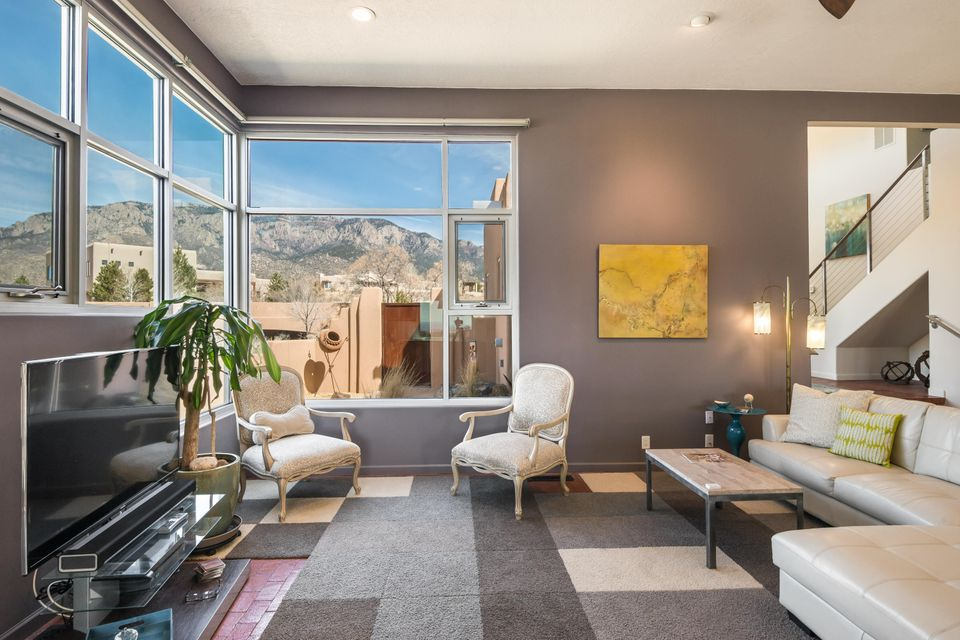 Contemporary perfection in High Desert!  This sleek, modern home offers every high end amenity imaginable, beautifully decorated and wrapped in New Mexico vistas from every direction on large lot.  Storefront windows, a pivoting front door and a large professionally landscaped walled yard are just a few upgrades that make this home a special place. A beautiful chef's kitchen equipped with Subzero refrigerator and ultra modern custom cabinets frame a view that spans over the city lights making this an entertainers dream.  The upstairs master suite, with mountain views, has a master bath that houses custom built in closets & cabinetry and unparalleled views creating a glorious retreat after a long day. 2 other bedrooms each with baths. Office/exercise room could be 4th bedroom.