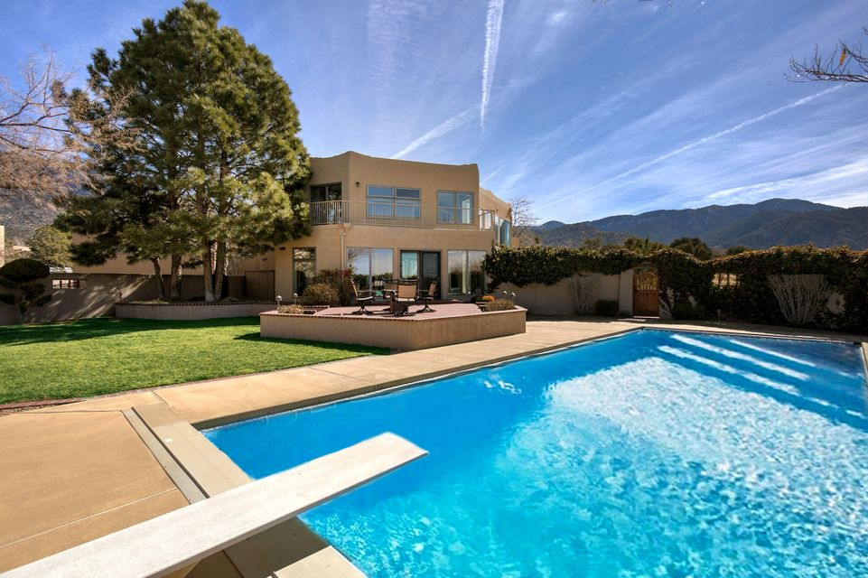 Impeccable custom home located in the beautiful foothills of the Sandia Mountains.This home showcases amazing views that you can enjoy from several locations inside and outside of the home. Indulge in the surrounding beauty of Sandia Heights from your gorgeous and private backyard while taking a dip in your heated, indground pool! You will enjoy the abundance of space this home has to offer with 5 bedrooms plus an extra room/office, a 784 sqft. finished basement with a wet bar, 2 living areas, formal dining room, 410 sqft. of sunroom space and so much more! Wait till you see the Gourmet kitchen w/Granite countertops, Stainless Steel appliances and plenty of cabinet space.This home also features Passive Solar & Solar Panels. A true beauty! This will not last, sellers are motivated to sell!