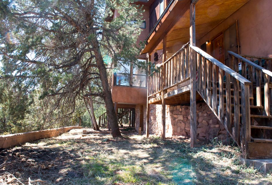 Great mountain home bordering National Forest.  Ideal 2400 SF floorplan  featuring 2 living areas, office, and large country kitchen.  Large detached 2 car garage. Heavily wooded lot. Home needs work but well priced for size/location.  Just minutes to ABQ !