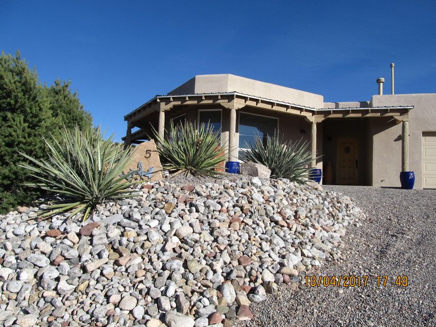 Beautiful, well-cared-for custom home perched on mesa top has expansive views into Colorado & northern NM. Professionally landscaped. Loads of outside space to enjoy. Portal wraps around home's front elevation. A walled patio extends the space--perfect for sitting out on summer evenings watching the sunset color the mountains. The back area allows for winter enjoyment within a warm, walled courtyard. Custom iron gates dress both exterior openings. Step inside to a large great room lit by picture windows & framed views. Kiva fireplace, beamed ceiling & 18'' tile floors dress the space. Kitchen looks into great room. Granite counter tops, knotty Alder cabinets & stainless appliances. Large master suite has hardwood floors, en-suite bath & walk-in closet. Private back courtyard access off MBR